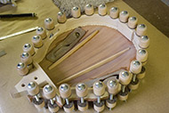 Traditional 'Violin' clamps are used to glue the front to the side-rib assembly. Excess glue is then cleaned up, the front is flexed, and the braces and front are fine-tuned to the final shape.