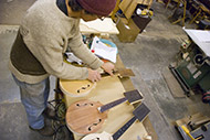 Fretboards are lined up and glued on, and the final shape of the headstock outline is marked and cut.