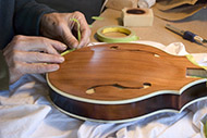 This redwood mandolin gets the perfiling accurately masked before the top is sprayed.